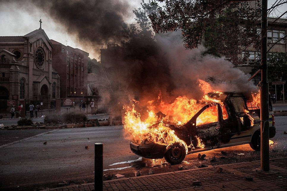 Горящий полицейский автомобиль во время студенческих протестов в ЮАР