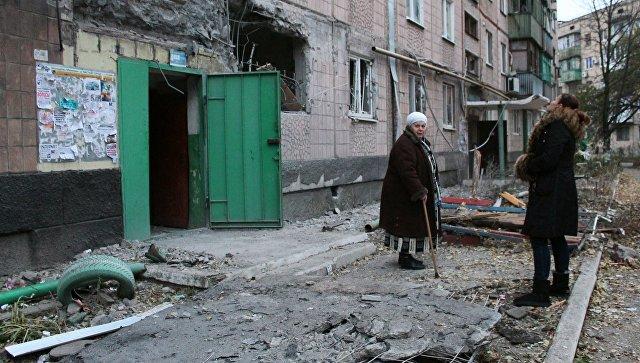 Жильцы у жилого дома, пострадавшего в результате обстрела украинскими силовиками, в Макеевке