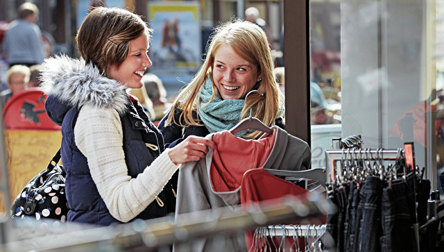 Девушки выбирают одежду для покупки. Архивное фото