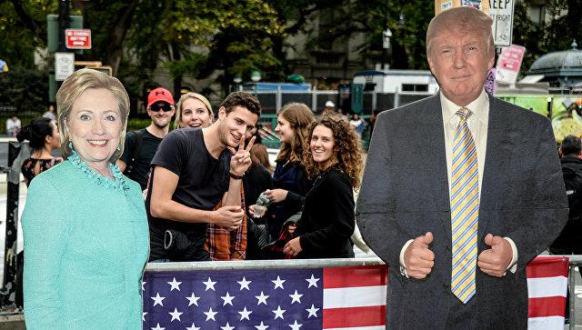 Молодые люди рядом с ростовыми фигурами кандидатов в президенты США в Нью-Йорке