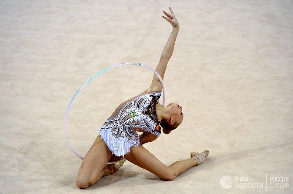 Яна Кудрявцева (Россия) выполняет упражнения с обручем в индивидуальных соревнованиях на чемпионате мира по художественной гимнастике в немецком Штутгарте
