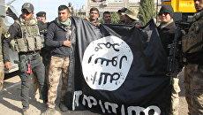 Бойцы Золотой дивизии фотографируются на фоне флага радикалов в Мосуле