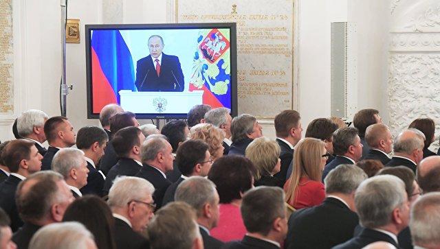 Экран с трансляцией выступления президента России Владимира Путина с ежегодным посланием Федеральному Собранию РФ в Георгиевском зале Кремля. 1 декабря 2016