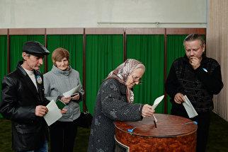 Женщина голосует на избирательном участке в Ташкенте во время выборов президента Узбекистана
