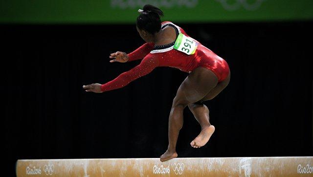Симона Байлз (США) выполняет упражнения на бревне в финале соревнований по спортивной гимнастике среди женщин на XXXI летних Олимпийских играх