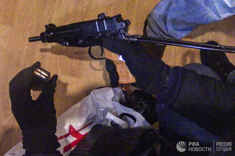 Сотрудник правоохранительных органов демонстрирует огнестрельное оружие и магазин с патронами к нему, изъятое сотрудниками ФСБ РФ у задержанной в Москве диверсионно-террористической группы