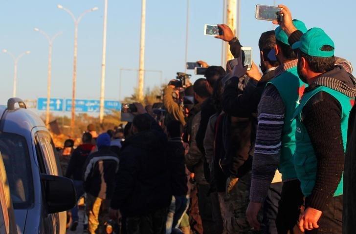 Боевики и мирные жители восточного Алеппо фотографируют колонну эвакуированных