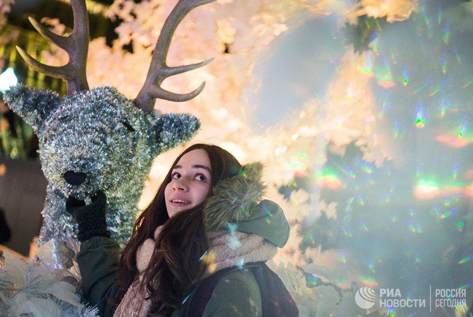 Девушка во время тестового включения световой новогодней инсталляции Музыкальный лес на Пушкинской площади в Москве