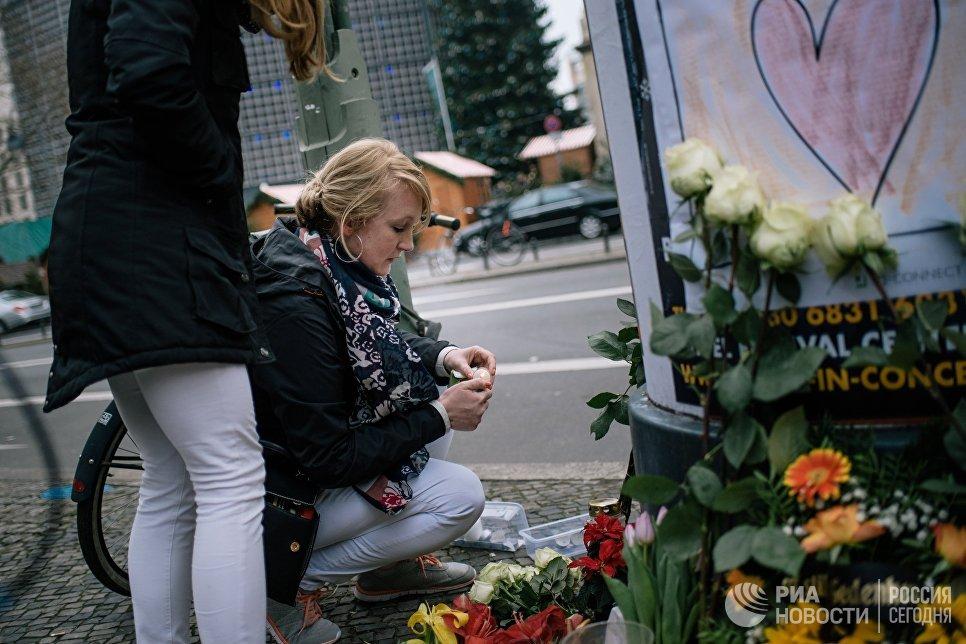 Девушка зажигает свечу недалеко от места теракта в Берлине. 20 декабря 2016