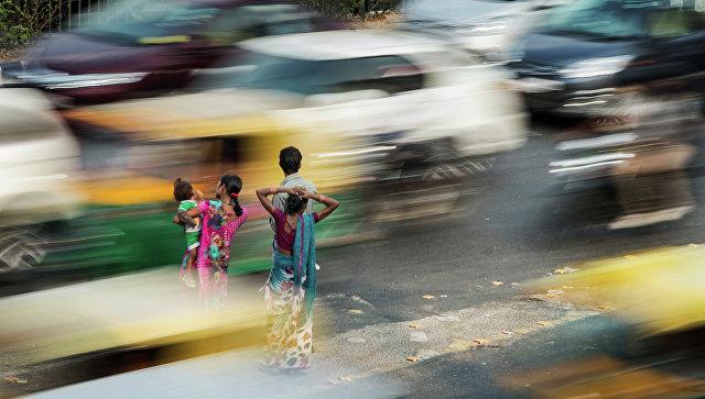 Люди стоят на разделительной полосе в час пик в Нью-Дели