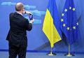 Человек фотографирует флаги Украины и Евросоюза
