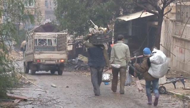 Мирные жители с мешками и сумками возвращаются домой в разрушенный Алеппо