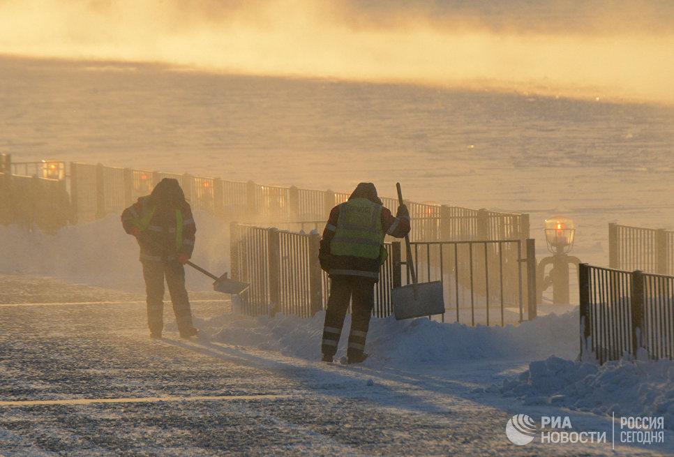 Работники городских служб убирают снег и наледь на Пушкинской набережной в Москве