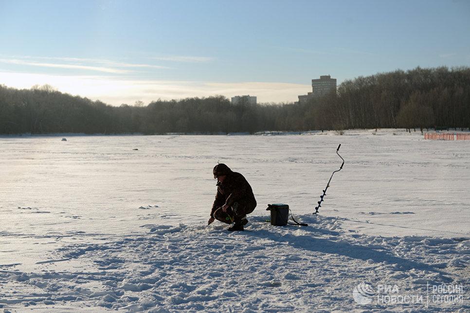 Рыбак ловит рыбу в Большом Садовом пруду на территории парка Сельскохозяйственной академии имени К. А. Тимирязева в Москве