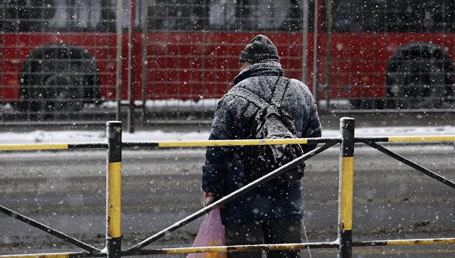 Мужчина стоит на остановке в морозный день в Белграде, Сербия. Январь 2017