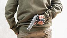 Мужчина с пистолетом за спиной. архивное фото