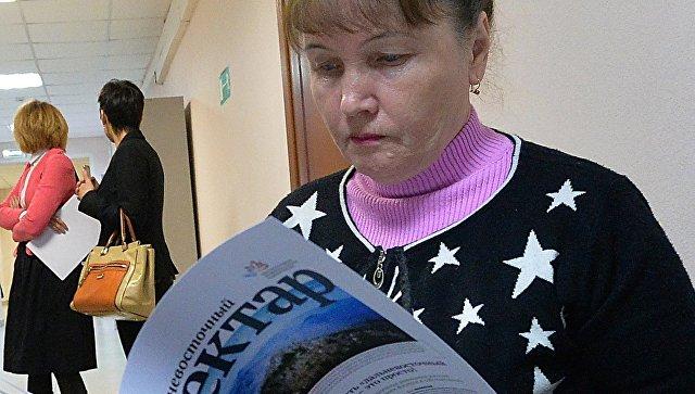 Жительница Приморья изучает информационный буклет в коридоре Департамента имущественных и земельных отношений Приморского края, где проходит вручение сертификатов на дальневосточные гектары. Архивное фото