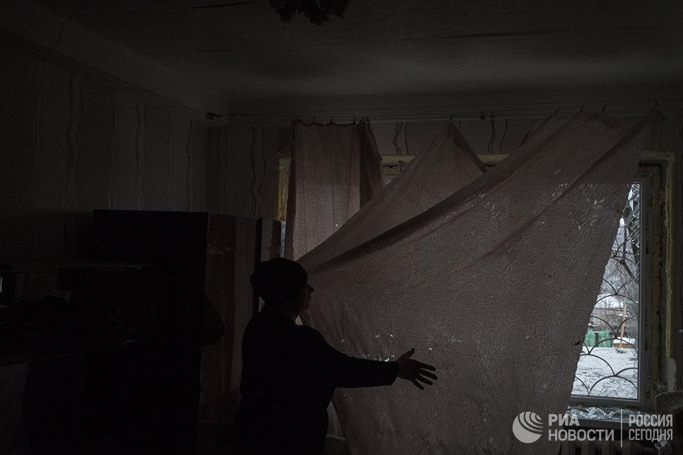 Женщина занавешивает поврежденное в результате обстрелов окно в Киевском районе Донецка