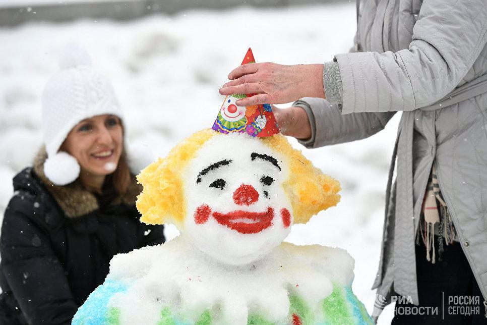 Участники украшают фигуру из снега во время Арт-битвы Снеговиков в Московском Дворце пионеров на Воробьевых горах