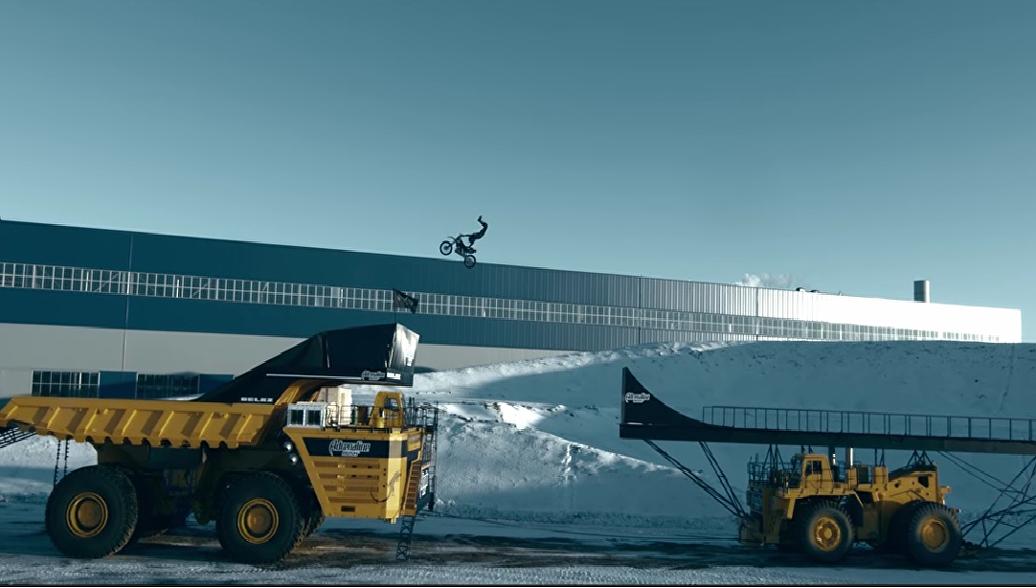 Прыжок мотофристайлера через движущиеся грузовики