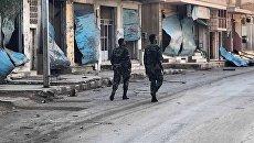 Солдаты у разрушенных в результате боевых действий домов в жилой части города Пальмира. Архивное фото