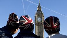 Мужчины в шапках с флагом Великобритании у здания парламента в Лондоне