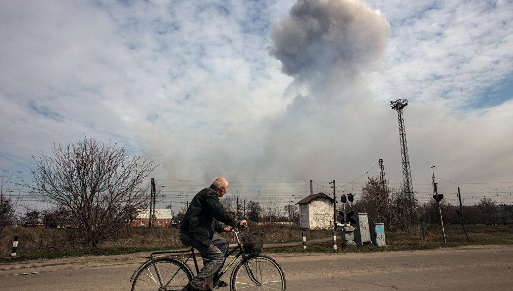 Мужчина на велосипеде на одной из улиц города Балаклея в Харьковской области во время пожара на военных складах боеприпасов