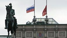 Приспущенные флаги над зданием Мариинского дворца в Санкт-Петербурге в память о погибших в результате взрыва в петербургском метрополитене