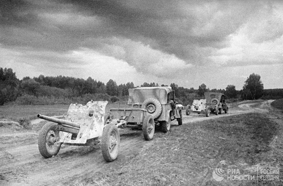 Машины ГАЗ-67 тянут по дороге артиллерийские орудия