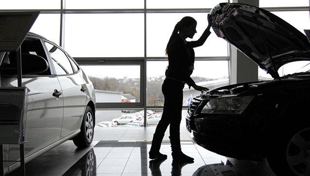Посетительница осматривает автомобиль в автосалоне. Архивное фото