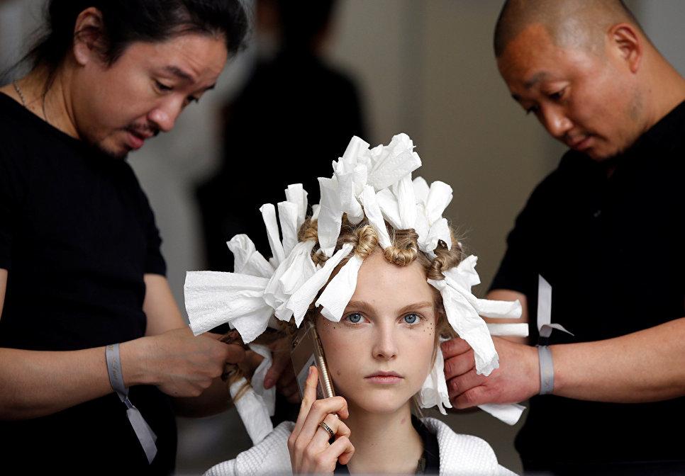 Стилисты делают прическу модели перед показом новой коллекции Christian Dior