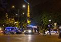 Сотрудники полиции стоят в оцеплении на месте перестрелки в Париже. Один полицейский погиб, еще один ранен при перестрелке в районе Елисейских полей в Париже