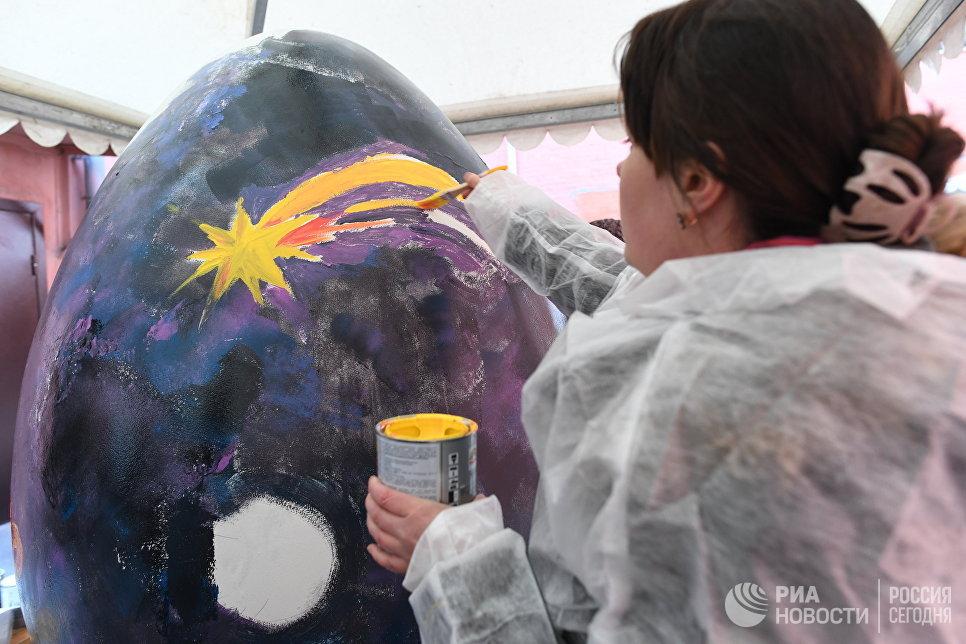 Участница расписывает пасхальное яйцо на арт-фестивале для журналистов МедиаПасха в Москве