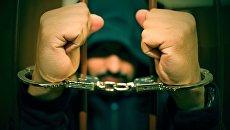 Мужчина в наручниках за решеткой. Архивное фото