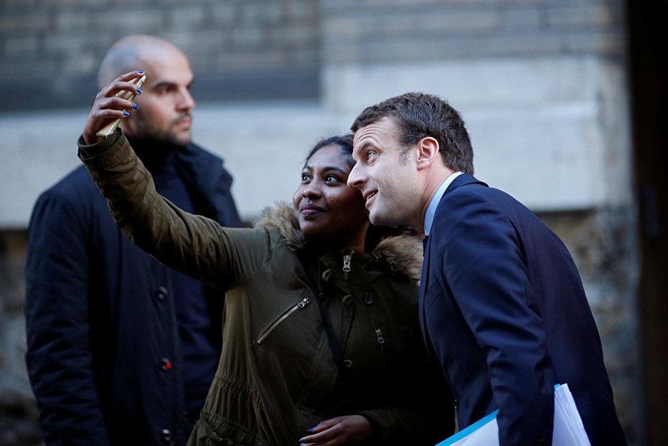 Кандидат в президенты Франции, лидер движения En Marche Эммануэль Макрон позирует для селфи у своего дома в Париже. 2 мая 2017 года
