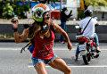 Участница марша против президента Венесуэлы Николаса Мадуро во время столкновений с полицией в Каракасе