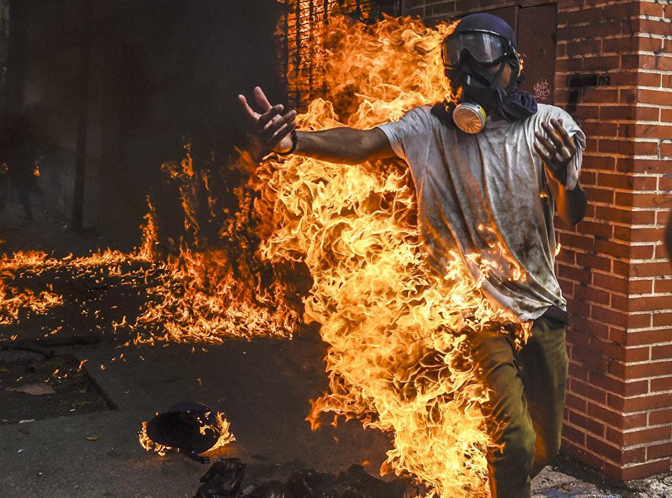 Демонстрант после взрыва бензобака полицейского мотоцикла во время столкновений в знак протеста против президента Венесуэлы Николаса Мадуро в Каракасе