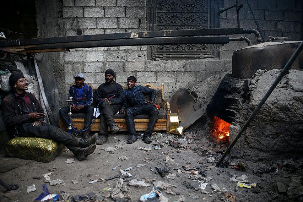 Сирийцы во время отдыха в мастерской в осажденном повстанцами городе Дума. 1 апреля 2017 года