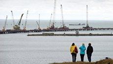 Люди наблюдают за строительством моста в Крыму. Архивное фото