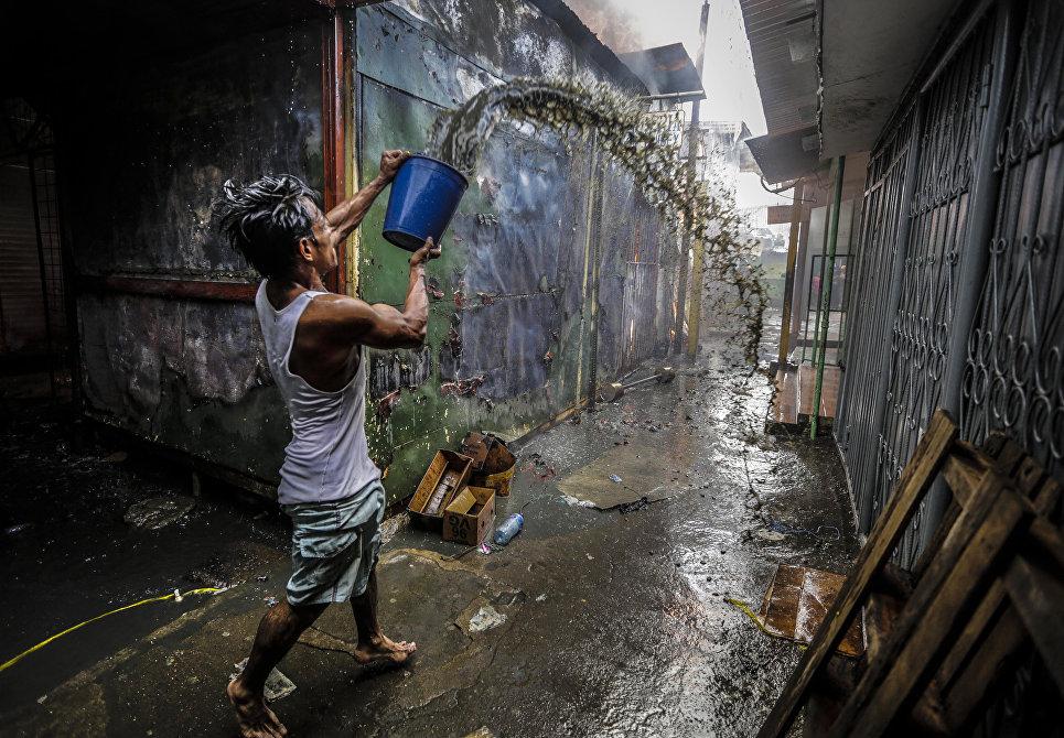 Мужчина помогает тушить пожар в Mercado Oriental в Манагуа, Никарагуа