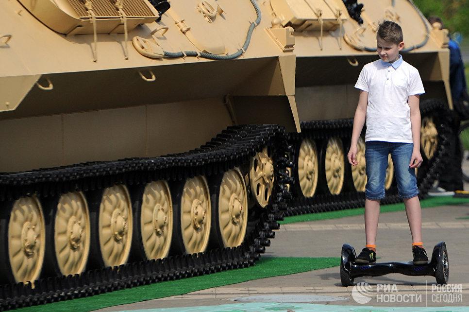Мальчик на гироскутере у военной техники на 8-й Международной выставке вооружения и военной техники Milex-2017 в Минске