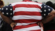 Толстый человек в футболке с флагом США