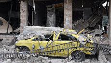 На месте взрыва автомобиля в квартале Аз-Захра в сирийском городе Хомс. 23 мая 2017