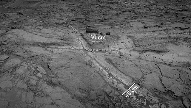 Трещины в породах впадины Бриджера на склонах марсианской горы Шарп где ученые открыли залежи песка