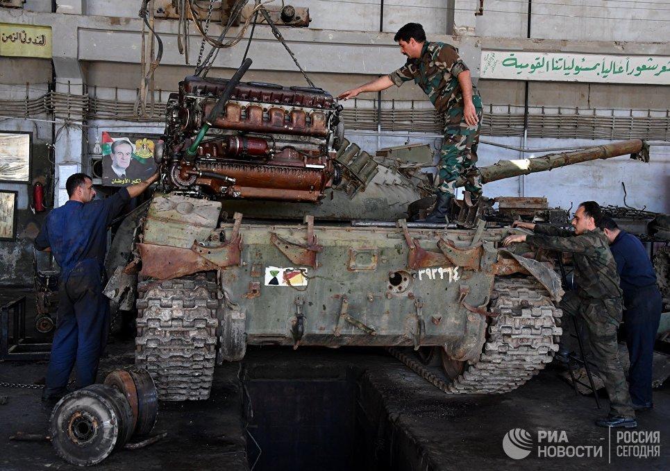 Рабочие устанавливают отремонтированный двигатель в одном из цехов завода по ремонту и восстановлению бронетанковой техники в Дамаске