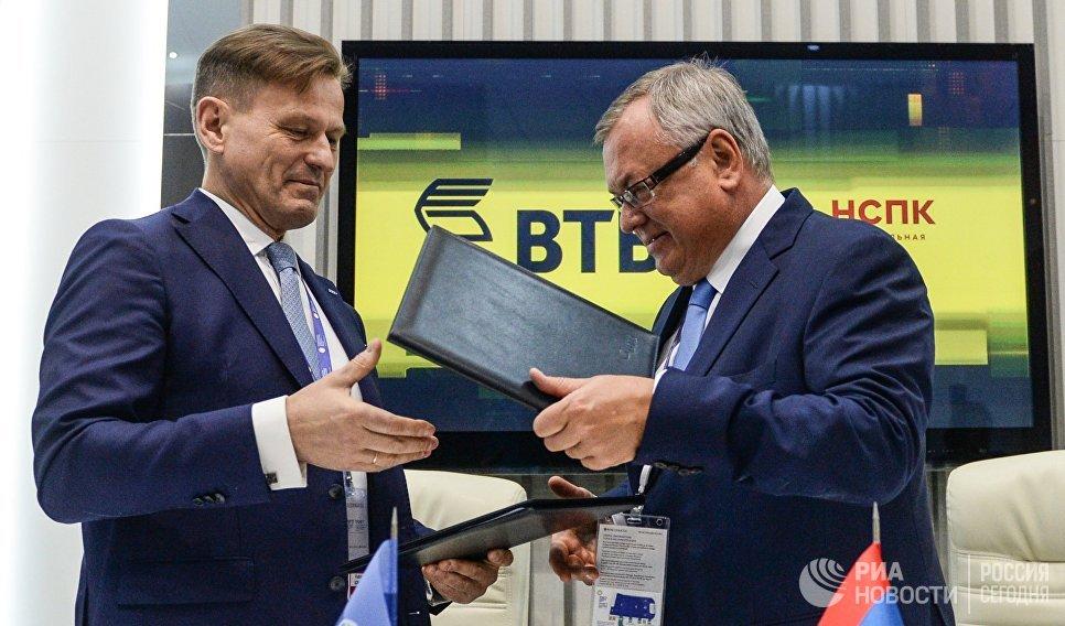 Генеральный директор АО Национальная система платежных карт Владимир Комлев и президент-председатель правления банка ВТБ Андрей Костин (справа) во время подписания соглашения в рамках Санкт-Петербургского международного экономического форума 2017