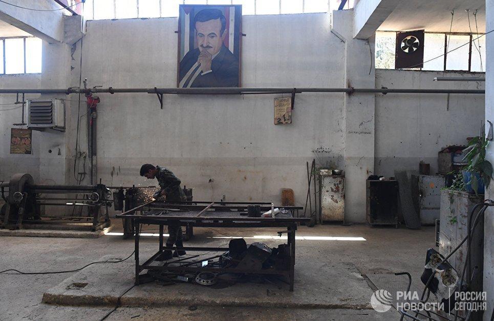 Рабочий в механическом цехе военного завода по изготовлению патронов в пригороде сирийского города Хам