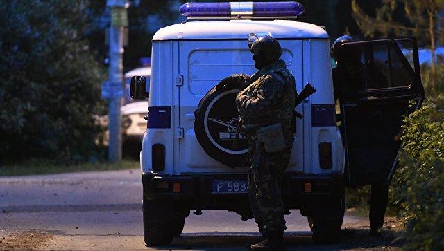 Сотрудники полиции стоят в оцеплении на одной из улиц поселка Кратово