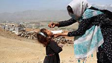 Медицинский работник вакцинирует ребенка в рамках кампании по борьбе с полиомиелитом в Афганистане. Архивное фото