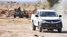 Самодельная пусковая ракетная установка сирийского ополчения (на втором плане) на передней линии фронта к востоку от города Пальмиры